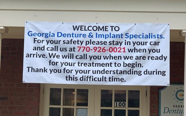 Dr. Warren Berne has a banner in front of his dental office explaining the change in waiting room procedure.