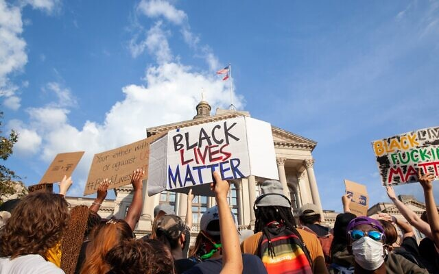 A protester holds a Black Lives Matter sign in front of the Georgia state capitol building. Protesters marched for the fifth straight day in Atlanta Tuesday, June 2, 2020.