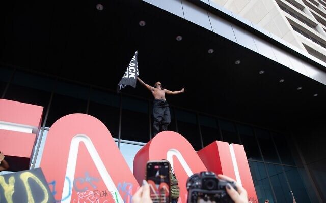 A protester holds a Black Lives Matter flag on top of the CNN sign in downtown Atlanta. Protesters and police clashed outside of the iconic CNN center May 29.