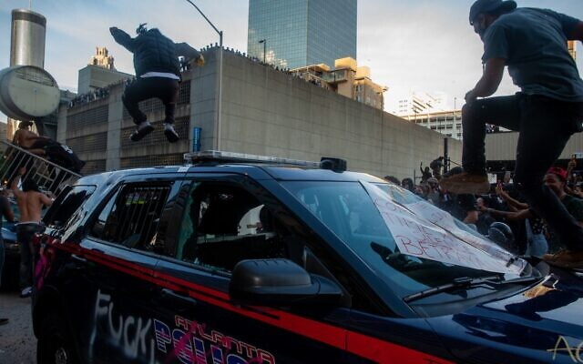 Protesters stomp on an Atlanta police vehicle left behind by police in front of the CNN center during a clash after the peaceful protest May 29.