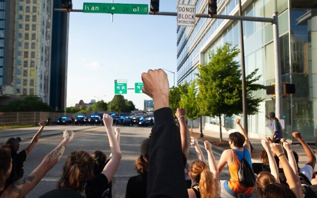 Protesters hold up their fists to Georgia state patrol officers, blocking off an entrance to Interstates 75 and 85 Saturday, May 20.