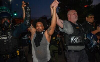 Lieutenant Knapp of the Atlanta police holds hands and marches with a protester in an attempt to get them to disband after a 9 p.m. curfew. Some protesters attempted to get others to leave Sunday, May 31