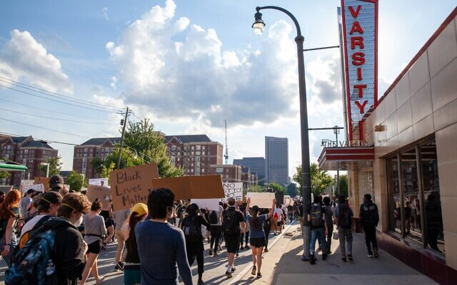 Protesters march by the Varsity downtown on the fourth day of protests Monday, June 1.