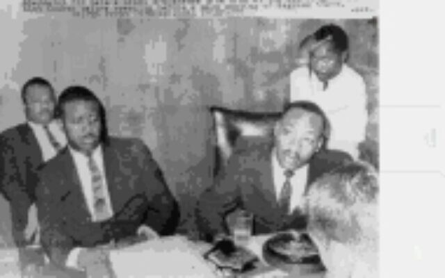 Strategy meeting: Johnson's grandfather Rev. N.H. Smith Jr., in white shirt, stands behind Martin Luther King at a strategy meeting with Rev. Ralph Abernathy and A.D. King, Dr. King's brother. Smith was one of Dr. King's chief strategists for the civil rights movement in Birmingham.