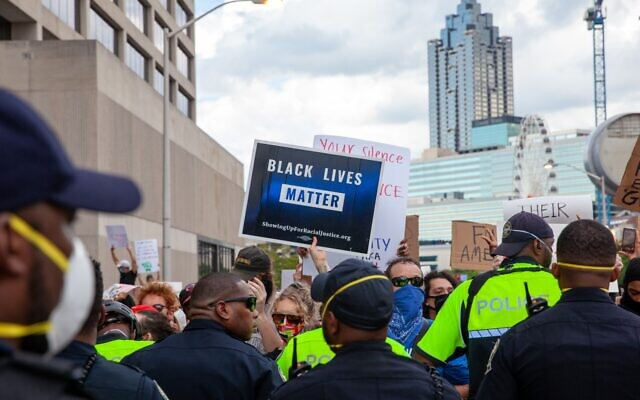Blue light from a police vehicle reflects off a Black Lives Matter sign held up by a protester during a clash with police after a peaceful protest Friday, May 29.