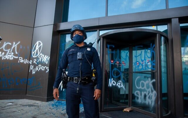 A police officer stands outside an entrance to the CNN center which has been coated with anti-police graffiti. Protesters broke windows of the building as they confronted police May 29.