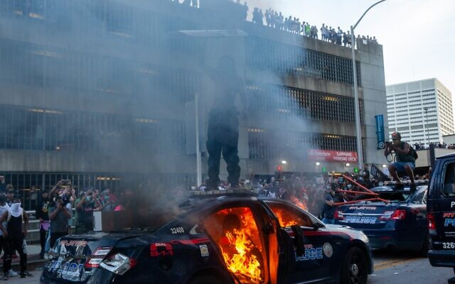 A protester stands on top of a burning police cruiser while holding a riot shield. Protests turned violent after a march over the death of George Floyd in front of the CNN Center and State Farm Arena May 29.