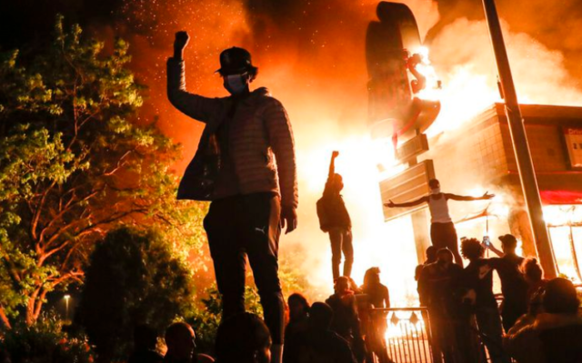 Protestors demonstrate outside of a burning fast food restaurant, Friday, May 29, 2020, in Minneapolis. Protests over the death of George Floyd, a black man who died in police custody Monday, broke out in Minneapolis for a third straight night. (John Minchillo/AP)