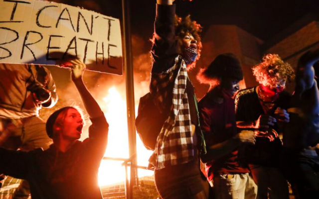 Protestors demonstrate outside of a burning Minneapolis 3rd Police Precinct, Thursday, May 28, 2020, in Minneapolis. Protests over the death of George Floyd, a black man who died in police custody Monday, broke out in Minneapolis for a third straight night. (John Minchillo/AP)