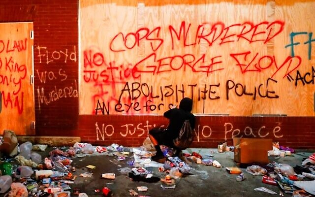 A protestor sprays graffiti on a wall near the Minneapolis 3rd Police Precinct, Thursday, May 28, 2020, in Minneapolis. Protests over the death of George Floyd, a black man who died in police custody Monday, broke out in Minneapolis for a third straight night. (John Minchillo/AP)