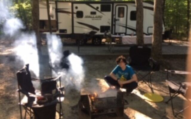 Doran Levin, 15, tends the campfire in front of the rented RV.