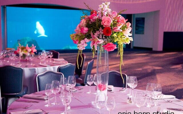 A wedding centerpiece at the Georgia Aquarium with snapdragon, roses, lilies, stock, and amaranthus (hanging greens).