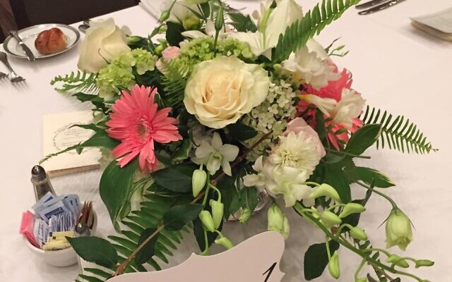 This centerpiece is made of roses, gerbera daisies, mini green hydrangea and greenery.