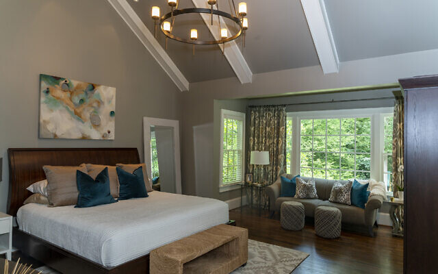 The vaulted ceiling in the master bedroom displays a Deeann Rieves ethereal vibe painting above the bed.