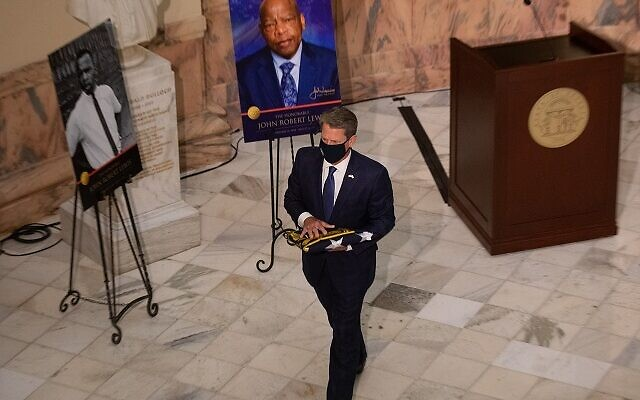 Governor Brian Kemp presents a Georgia state flag to John Lewis's son as the late John Lewis lays in state at the Georgia state capitol in Atlanta, Georgia on July 29th. // Nathan Posner AJT