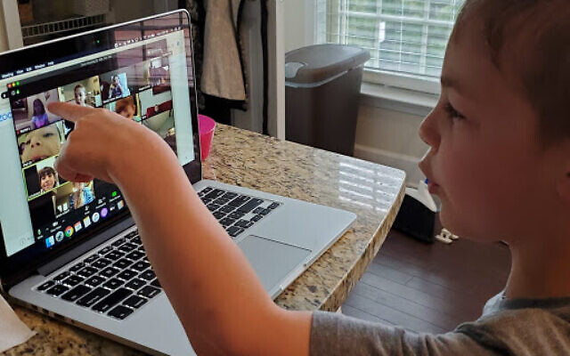 First-grader Reuven Simon learns online at home.