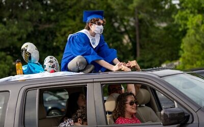 Ari Slomka sits on the roof of the family car holding hands with his parents.