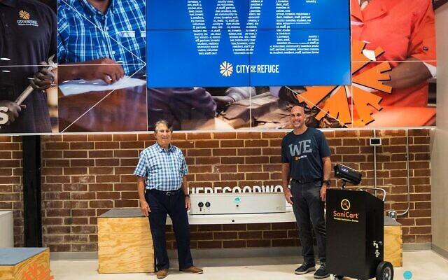 Itamar Kleinberger presents sanitizing equipment to Scott Steiner of City of Refuge.