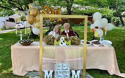 Mira Bergen and Michael Mann pose inside an empty frame, among the curbside engagement party decorations.