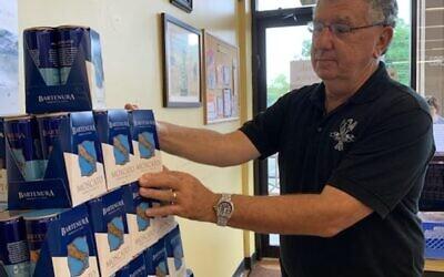 Steve Gilmer stocks the shelves at Kosher Gourmet for the upcoming holidays.