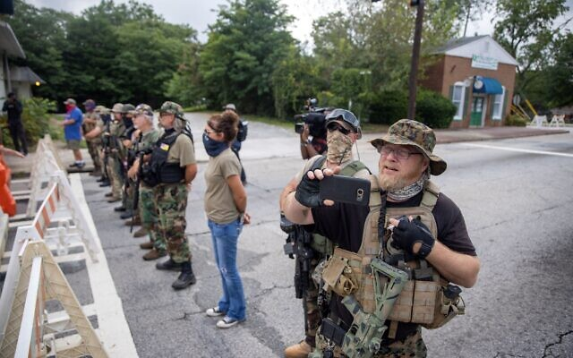 Members of the III% militia of Georgia, including leader Chris Hill, stand on the street in opposition to counter-protesters.// Nathan Posner of AJT