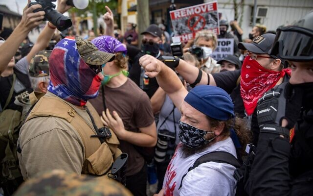 A counter-protester throws his fist in the air as militia members face off against counter-protesters in downtown Stone Mountain. // Nathan Posner of AJT
