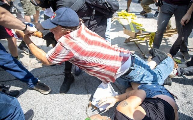 Protesters fight over a Confederate flag with a pro-Stone Mountain supporter at Heritage Not Hate protest.// Nathan Posner of AJT