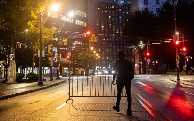 A black bloc protester moves a mobile fence in downtown Atlanta as protesters move towards the Zone 5 precinct. // AJT's Nathan Posner