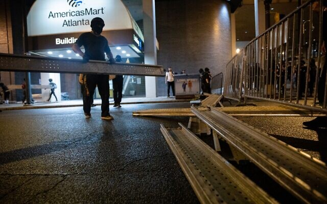 A black bloc protester moves a steel bar to help set up a barricade in front of the Zone 5 precinct in downtown Atlanta. // AJT's Nathan Posner