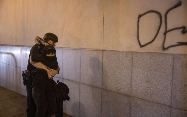 An Atlanta police officer grabs a protester in an attempt to arrest her, after she spray painted the side of the Zone 5 precinct. // AJT's Nathan Posner