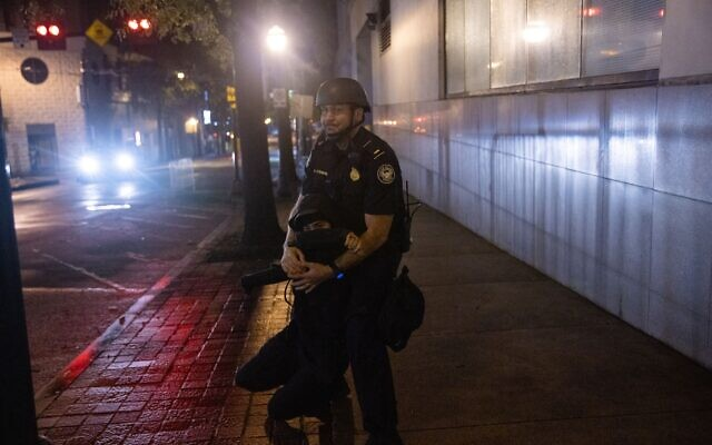 An Atlanta police officer grabs a protester in an attempt to arrest her after she spray painted the side of the Zone 5 precinct. // AJT's Nathan Posner