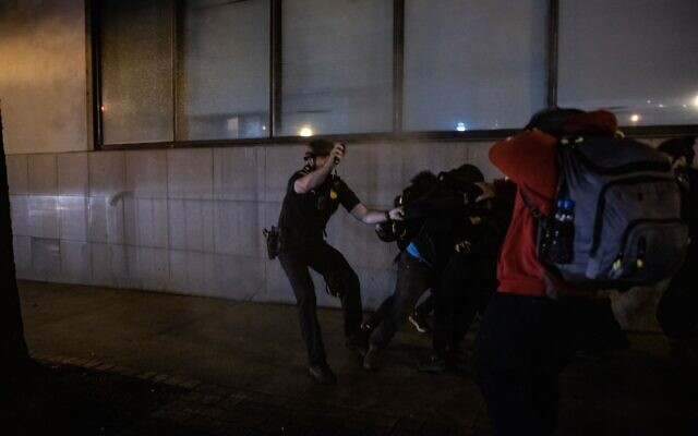 An Atlanta police officer uses pepper spray on protesters after he is unable to arrest a woman who was spray painting the side of the Zone 5 precinct building. // AJT's Nathan Posner