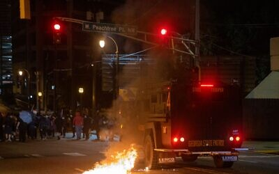 A Georgia State Patrol vehicle moves towards protesters as an officer fires rubber bullets and pushes past a fire caused by a Molotov cocktail. // AJT's Nathan Posner