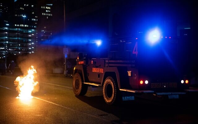 An officer fires rubber bullets and pushes past a fire caused by a Molotov cocktail as a  Georgia State Patrol vehicle moves towards protesters. // AJT's Nathan Posner
