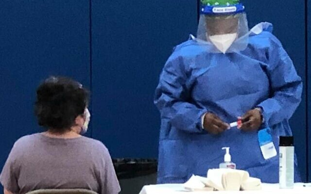 Photo by Barrie Cohn, AJA marketing director // Nareen Bennett, Jewish HomeLife's director of quality assurance (in blue PPE), administering COVID-19 testing at Atlanta Jewish Academy.