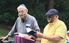 Rabbi Michael Kramer and Allen Lipis test unamplified sound while praying from an outdoor podium.