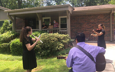 Gus Garay, his daughter Liz and friend Julia Johnson on flute entertain Paula and Bill Gris in front of their home.