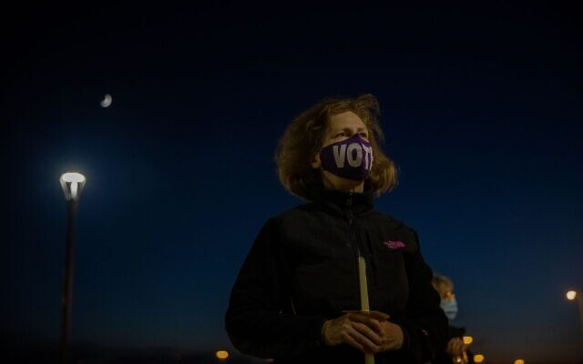 A woman holds a candle in memory of the late Justice Ginsburg at a candlelight vigil in her memory. // Nathan Posner for the AJT.