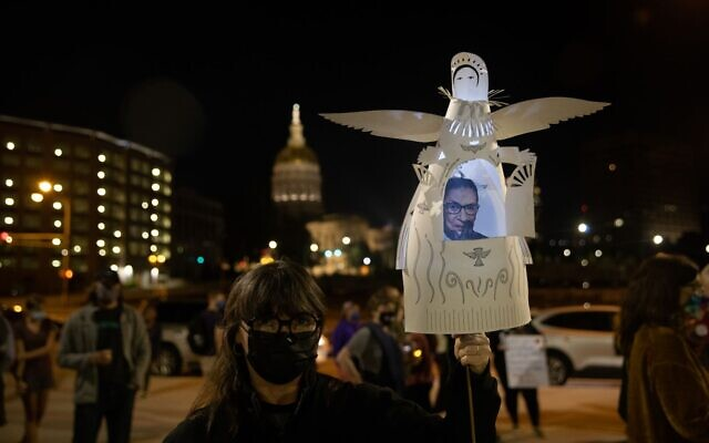 A mourner holds a cutout angel with the late Justice Ginsburg pictured inside, with a sign honoring the late justice visible in the background at a candlelight vigil in the late justice's honor. // Nathan Posner for the AJT.