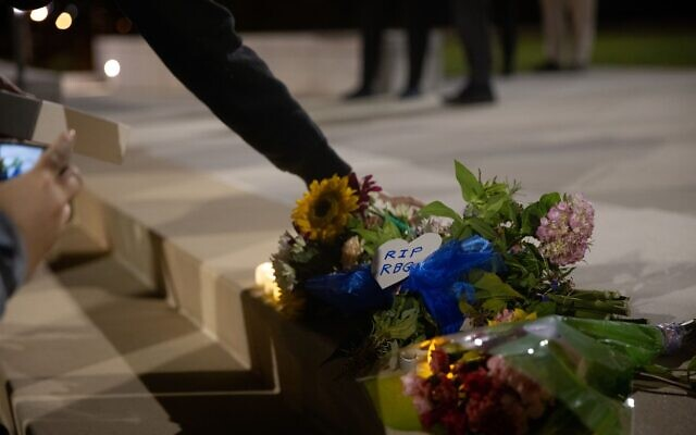 People place candles and flowers at a makeshift memorial honoring the late Supreme Court Justice Ruth Bader Ginsburg at the Georgia Supreme Court building. // Nathan Posner for the AJT.