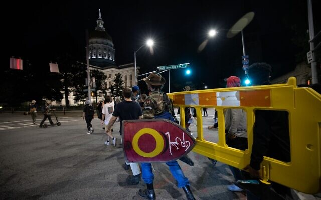Protestors move barricades as they return to the Georgia Capitol building around 9:40 p.m. on the evening of Sept. 23. // Nathan Posner for the AJT.