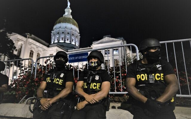 Atlanta police officers let their guard down after protests dispersed in front of the Georgia State Capitol Building. // Nathan Posner for the AJT.