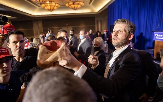 Eric Trump signs a hat at a rally in support of his father near Atlanta's main airport. // AJT Nathan Posner