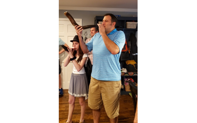 Josh Needle blows shofar at Sunrise Senior Living with his daughter Bess.