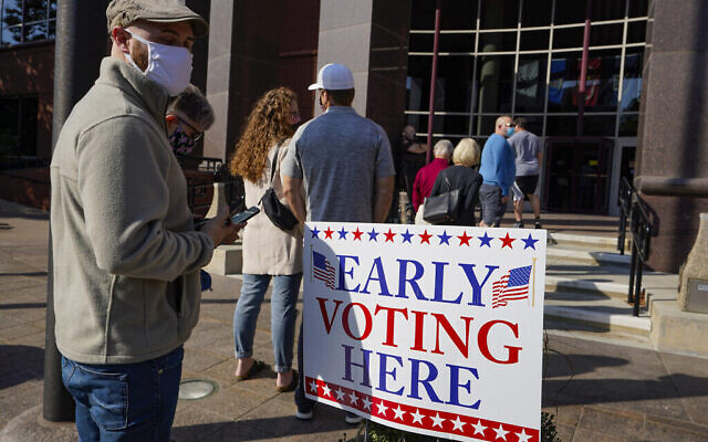 Voters wait in line at the Judicial Center in Noblesville, Ind., Wednesday, Oct. 7, 2020, to cast their ballot on the second day of early voting in Indiana. (AP Photo/Michael Conroy)