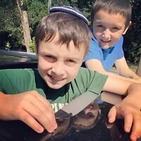 Feldman's two sons pop out of the car's sunroof to hear the shofar blowing at a drive-through service in AA's parking lot.