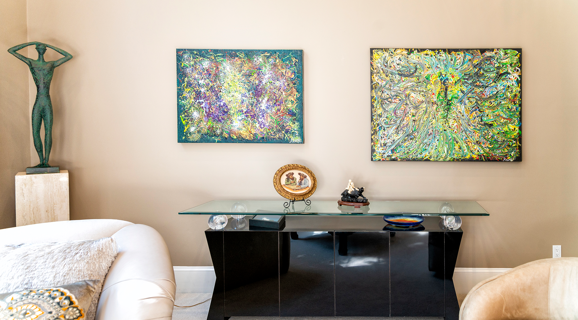 """Duane Stork // The north side of the living room is adorned by two of Printz's acrylics on canvas: 36-by-48 inch """"Blue Dog,"""" right, and 30-by-40 inch """"Lake,"""" left, both layered in the style of Jackson Pollock."""