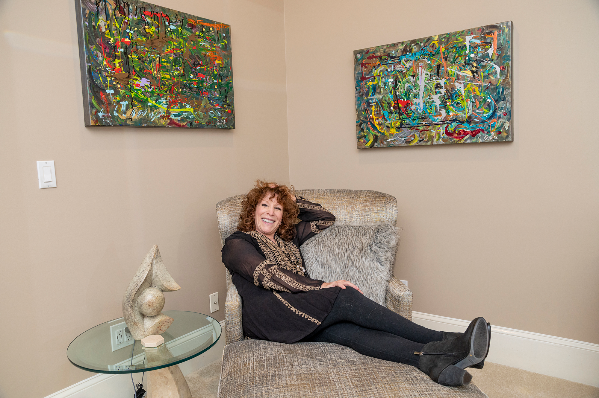 """Duane Stork // Abstract expressionist artist Gayle Printz relaxes with two of her paintings in the background. """"Pond,"""" left, and """"Friend."""" """"Pond"""" was one of the two works selected for the Paris museum display along with """"First."""""""