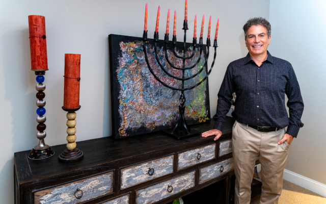 "Duane Stork // Steven Printz poses by the couple's handmade, wrought iron menorah in front of Gayle's painting ""Metallic."" Steven's own photography is showcased at home and on Gayle's website."