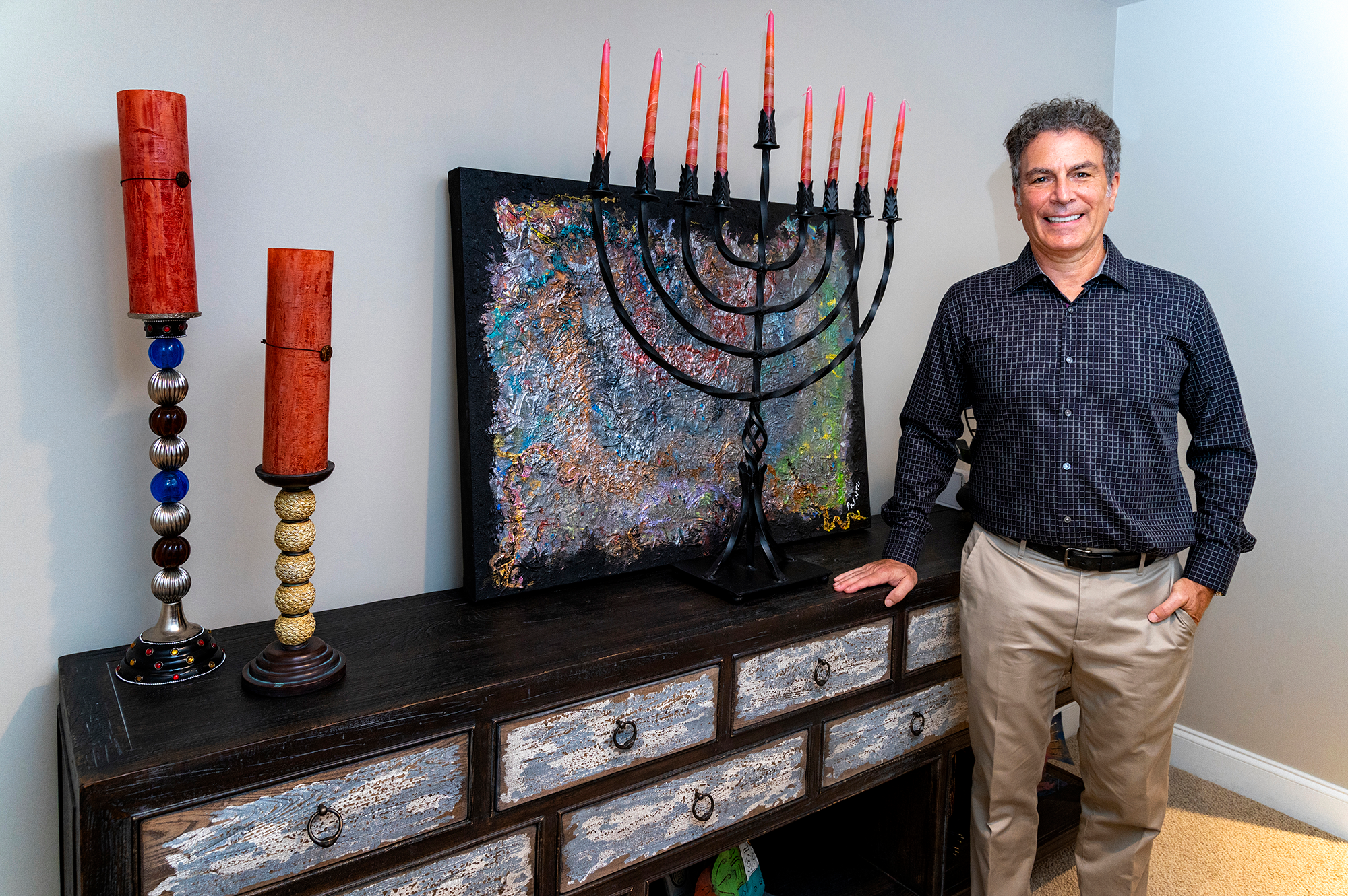 """Duane Stork // Steven Printz poses by the couple's handmade, wrought iron menorah in front of Gayle's painting """"Metallic."""" Steven's own photography is showcased at home and on Gayle's website."""